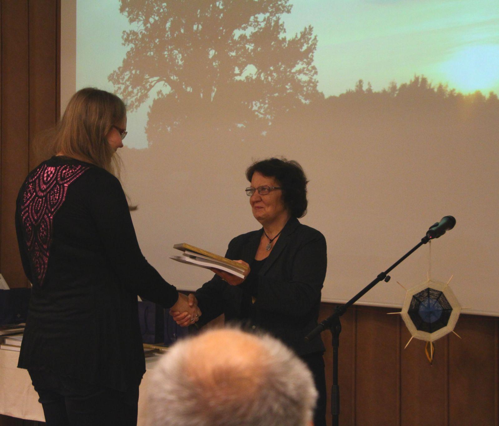 Ilme Mäesalu annab Kadriliis Rämmannile yle Muinsuskaitseameti eriauhinna